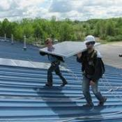 Workers carry solar panels onto the roof of the Kent State Field House
