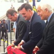 Ribbon cutting in Akron with Don Plusquellic nearest the camera and Sherrod Brown on the far end