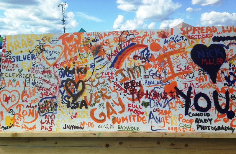 An interactive display allows festival goers to leave messages on a wooden wall.